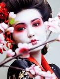 Geisha bonito joven en kimono negro entre Sakura, ethno asiático Imágenes de archivo libres de regalías