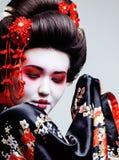 Geisha bonito joven en kimono negro entre Sakura, ethno asiático Imagen de archivo libre de regalías