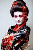 Geisha bonito joven en kimono negro entre Sakura, ethno asiático Fotografía de archivo