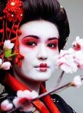 Geisha bonito joven en kimono negro entre Sakura, ethno asiático Imagen de archivo