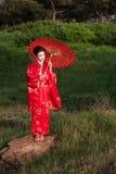 Geisha in den grünen Hügeln am Sonnenuntergang Lizenzfreie Stockfotos
