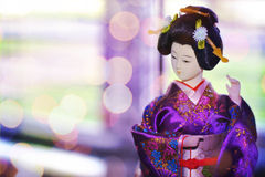 Geisha doll on purple background royalty free stock photography