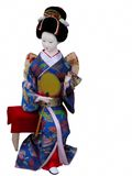Geisha doll sitting. Geisha doll with paper fan sitting on a bench, isolation over white background Stock Photography