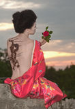 Geisha with dragon tattoo. Sitting on the rocks - looking at rose in sunset time royalty free stock photography