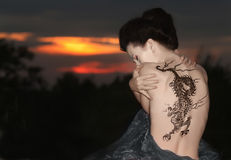 Geisha with dragon tattoo. Sitting on the rocks - looking at rose in sunset time royalty free stock images