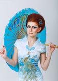Geisha in einem schicken Kleid mit Regenschirm Stockfotografie