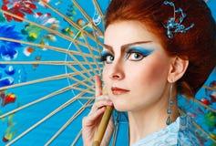 Geisha in einem schicken Kleid mit Regenschirm Lizenzfreies Stockfoto