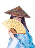 Geisha with fan. Beauty geisha in blue kimono hide behind fan with hieroglyphs isolated on white background Stock Photos