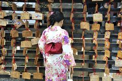 Geisha in front of prayer tablets. Kyoto, japan-November 4, 2014; Geisha in front of prayer tablets at Rokuharamitsuji Temple. People write their wish on a stock photo