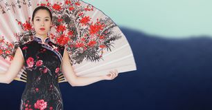 Geisha with giant fan against blurry mountain Stock Images