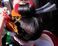 Geisha hairstyle. Two hands dressing a geisha's hair during an important street event in Gion(geisha's ward in Kyoto,Japan).The light play is something very Royalty Free Stock Photo