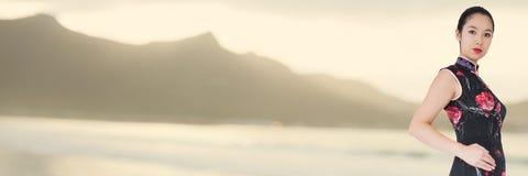 Geisha with hand on hip against blurry yellow coastline Stock Photo