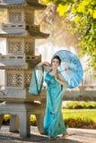 Geisha hermoso con un paraguas azul Fotos de archivo