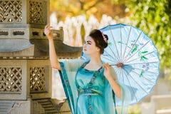 Geisha hermoso con un paraguas azul Imagen de archivo libre de regalías