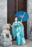Geisha hermoso con un paraguas azul Imagenes de archivo