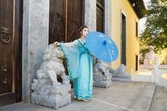 Geisha hermoso con un paraguas azul Foto de archivo