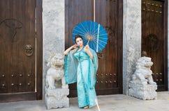 Geisha hermoso con un paraguas azul Imágenes de archivo libres de regalías