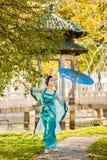 Geisha hermoso con un paraguas azul cerca del manzano verde Imagen de archivo libre de regalías