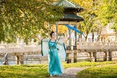 Geisha hermoso con un paraguas azul cerca del manzano verde Fotografía de archivo