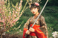 Geisha hermoso en kimono con la espada del samurai foto de archivo libre de regalías