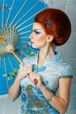 Geisha i en smart klänning med paraplyet Fotografering för Bildbyråer