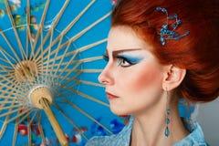 Geisha i en smart klänning med paraplyet Royaltyfria Bilder