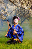 Geisha. Japanese geisha in blooming cherry garden Royalty Free Stock Photos