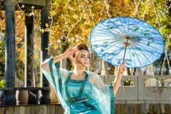 Geisha joven hermoso con un paraguas azul Foto de archivo