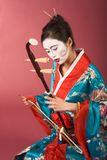 Geisha in kimono with erhu. Asian female with geisha style face paint in yukata (kimono) playing erhu Stock Photography