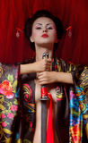 Geisha in kimono with samurai sword Royalty Free Stock Image
