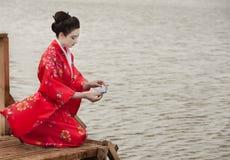 Geisha launches origami bird Stock Photos