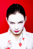 Geisha make up on woman. Portrait of pretty black haired woman wearing Japanese Geisha style white face powder, red background Stock Image