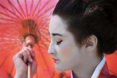 Geisha mit rotem Regenschirm Stockfotos
