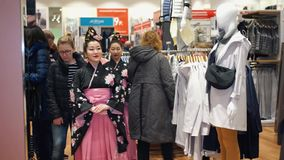 Geisha. Moscow, Russia - March 5, 2017: Geishas walking in the UNIQLO clothing store among the clothing goods and ordinary consumers. Performance is timed to the stock video footage
