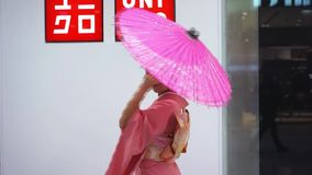 Geisha. Moscow, Russia - March 5, 2017: Geisha in traditional Japanese kimono with umbrella at the entrance to the uniqlo store. Performance is timed to the stock video