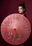 Geisha with traditional painted umbrella. Geisha holding a beautiful red umbrella. studio shot Royalty Free Stock Image