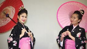 Geisha. Two beautiful geishas in a traditional japanese kimono smiling and twisting parasols