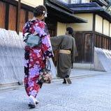 Geisha walking with man Royalty Free Stock Image