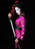 Geisha warrior pulls out sword of sheath Stock Photo