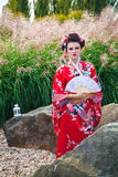 Geisha woman with a fan in garden Stock Photo