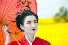 Geisha in the yellow field. Geisha in red kimono in the yellow field. Professional make-up, traditional hairstyle Stock Photography