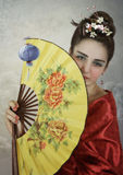 The Geisha. The young girl in red kimono with fan in her hand royalty free stock photography