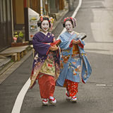 Geishas. Kyoto, Japan - MAY 9, 2010: Unidentified Geishas walking by an old street and speaking in Gion district, Kyoto, Japan Royalty Free Stock Photo