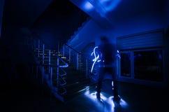 Geist im Geisterhaus an der Treppe, mysteriöses Schattenbild des Geistmannes mit Licht an der Treppe, Horrorszene furchtsamer Gei stockfotografie