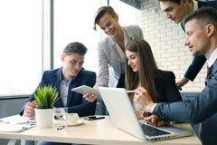geistesblitz Gruppe Geschäftsleute, die zusammen den Laptop betrachten Eine Geschäftsfrau, die Kamera betrachtet lizenzfreies stockfoto