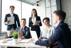 geistesblitz Gruppe Geschäftsleute, die zusammen den Laptop betrachten Eine Geschäftsfrau, die Kamera betrachtet stockfoto