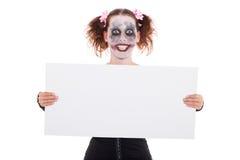Geisteskranker lächelnder weiblicher Clown mit Zeichen Stockfoto