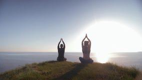 Geistige Welt, Mann und Frau, die auf den Berg betrachtet das Meer meditiert in Lotussitz auf Land, die Ansicht sitzt stock video footage