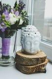 Geistiges Ritualmeditationsgesicht von Buddha auf weißem Hintergrund Rustikal, blüht Frühlingsblumenstrauß Butterblume Ranunculus Stockbilder