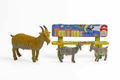 Geit plastic speelgoed met houten bank op een witte achtergrond Stock Foto